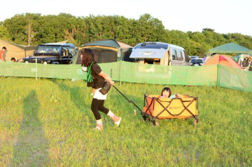 子どもが乗ったキャリーカートを引っ張るお母さん